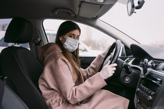 Jovem mulher com uma máscara e luvas dirigindo um carro.