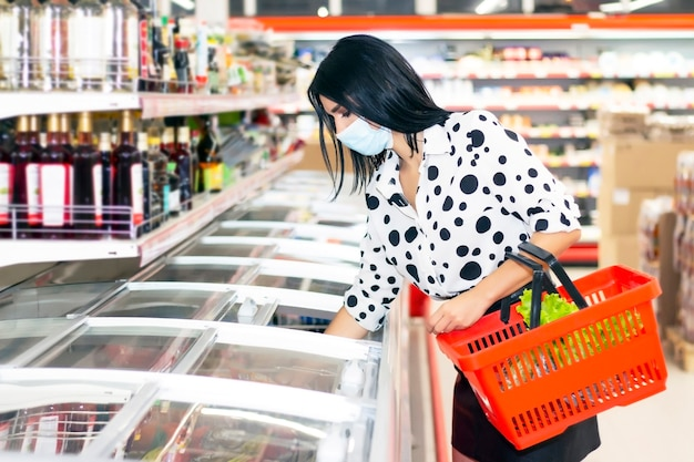 Jovem mulher com uma máscara médica descartável está fazendo compras no supermercado.