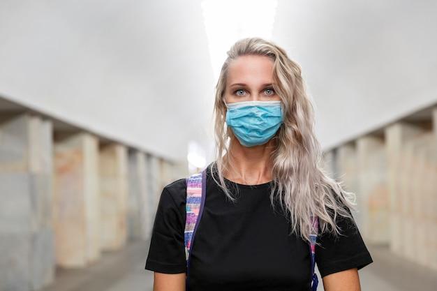 Jovem mulher com uma máscara médica no saguão do metrô. loira linda com cabelo comprido em uma camiseta preta.