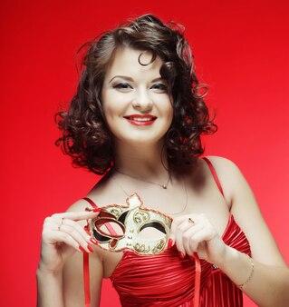 Jovem mulher com uma máscara misteriosa vermelha