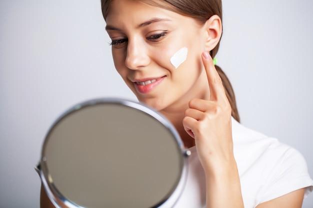 Jovem mulher com uma pele bonita coloca creme hidratante no rosto