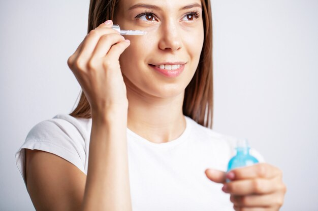 Jovem mulher com uma pele bonita coloca vitaminas no rosto