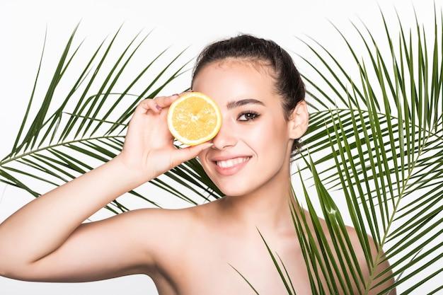 Jovem mulher com uma pele perfeita, segurando citrinos na mão, rodeado por palmeiras deixa isolado na parede branca