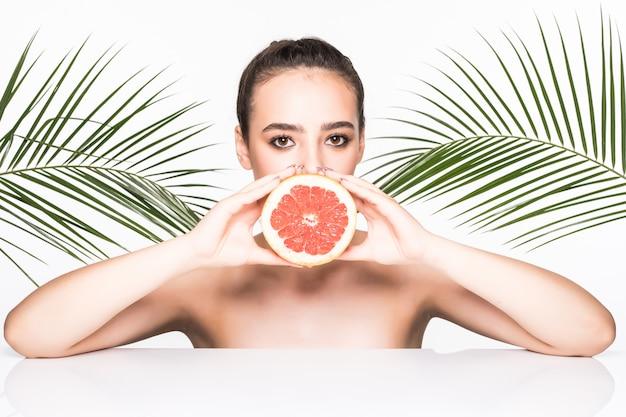Jovem mulher com uma pele perfeita, segurando frutas cítricas nas mãos, rodeadas por palmeiras deixa isolado na parede branca
