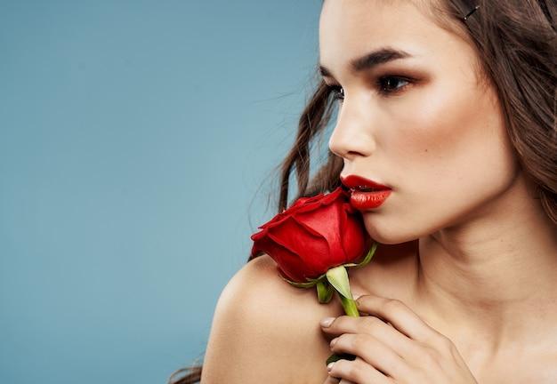 Jovem mulher com uma rosa vermelha perto da sombra do rosto no modelo de fundo azul de pálpebras. foto de alta qualidade