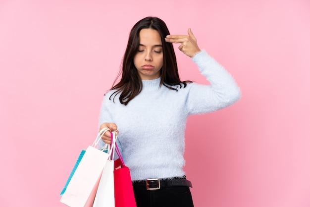 Jovem mulher com uma sacola de compras com problemas fazendo gesto de suicídio