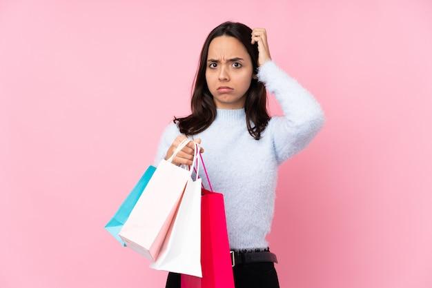 Jovem mulher com uma sacola de compras na parede rosa com dúvidas