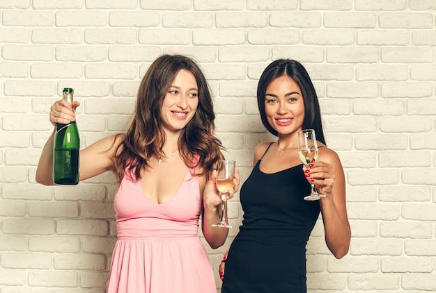 Jovem mulher com uma taças de champanhe em comemoração