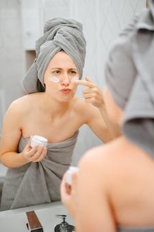 Jovem mulher com uma toalha de banheiro cinza aplica um creme de rugas nas bochechas. conceito de cosmetologia em casa.