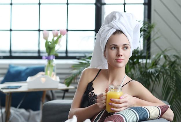 Jovem mulher com uma toalha na cabeça e suco de laranja