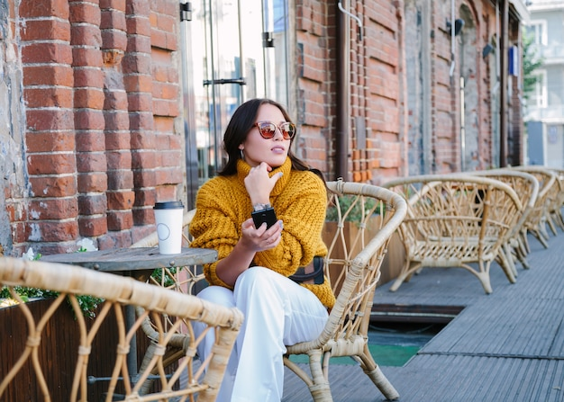Jovem mulher com uma xícara de café ao ar livre