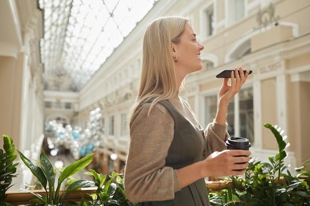 Jovem mulher com uma xícara de café gravando mensagem de áudio em seu telefone celular enquanto caminhava pelo belo edifício