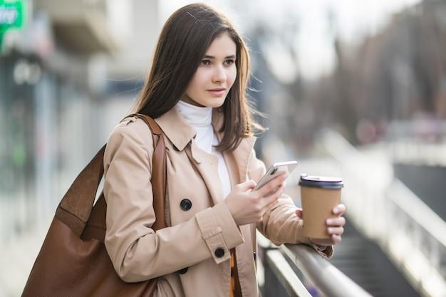 Jovem mulher com uma xícara de café no telefone na cidade