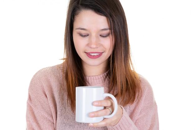 Jovem mulher com uma xícara de café olha para baixo pensativo