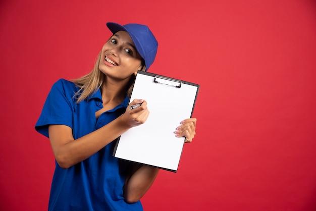 Jovem mulher com uniforme azul, apontando para a área de transferência com um lápis.