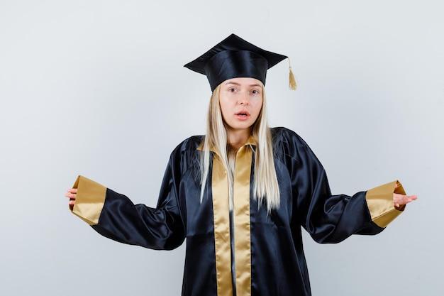 Jovem mulher com uniforme de pós-graduação, mostrando um gesto desamparado e parecendo confusa Foto gratuita