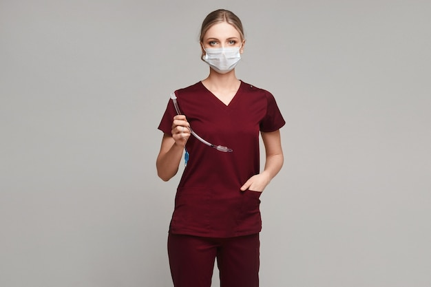 Jovem mulher com uniforme médico e máscara médica posando com um tubo endotraqueal no fundo cinza, isolado. conceito de saúde e emergência.