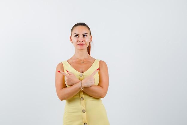 Jovem mulher com vestido amarelo, apontando para o lado com os braços cruzados e olhando pensativa, vista frontal.