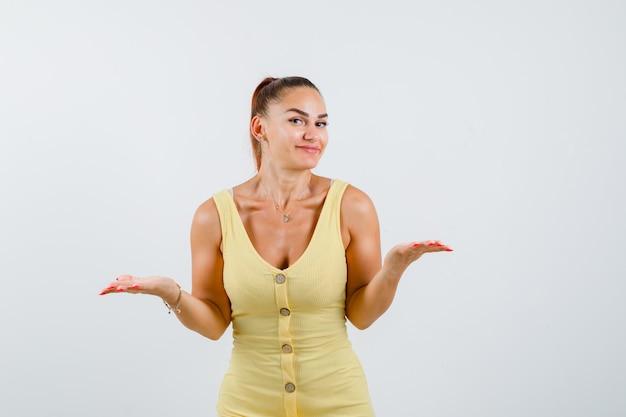 Jovem mulher com vestido amarelo, espalhando as palmas das mãos e olhando curiosa, vista frontal.