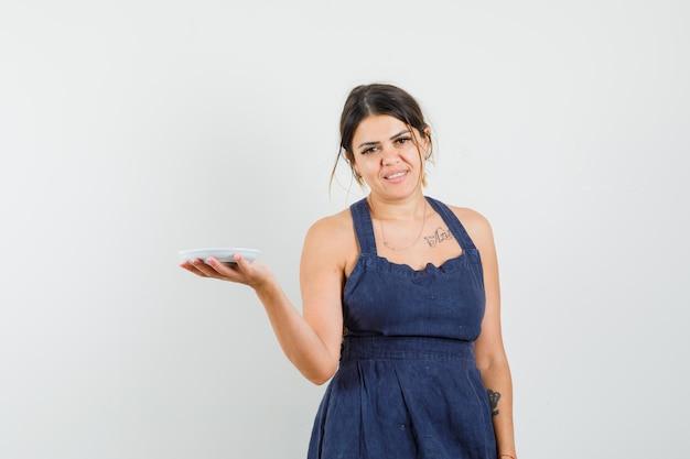 Jovem mulher com vestido azul escuro segurando um pires vazio e parecendo alegre