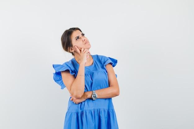 Jovem mulher com vestido azul olhando para cima e parecendo pensativa