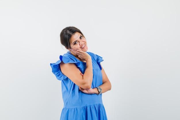 Jovem mulher com vestido azul, posando de pé e parecendo alegre