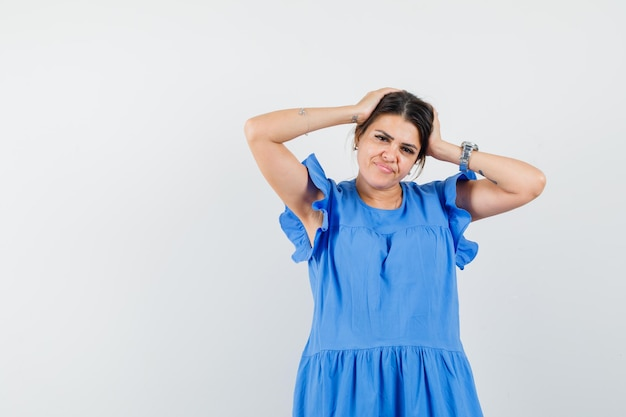 Jovem mulher com vestido azul, segurando a cabeça com as mãos e parecendo hesitante