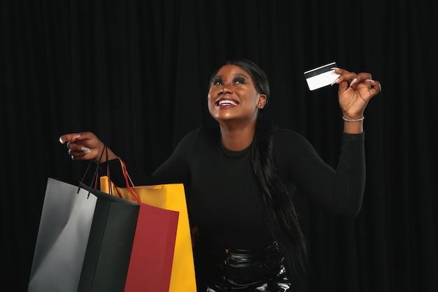 Jovem mulher com vestido comprando em fundo preto