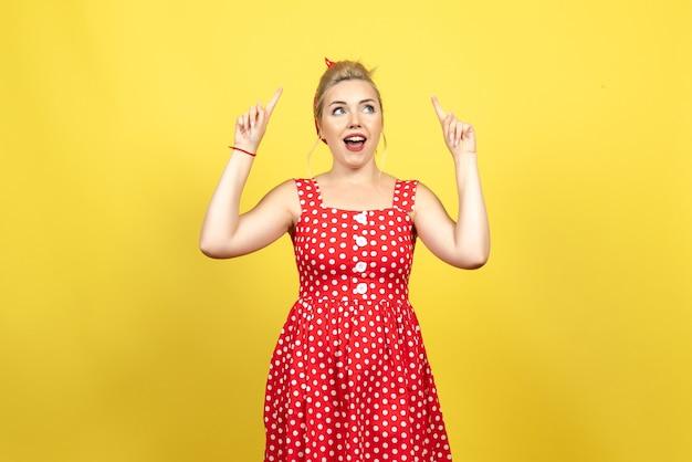 Jovem mulher com vestido de bolinhas vermelhas levantando os dedos em amarelo