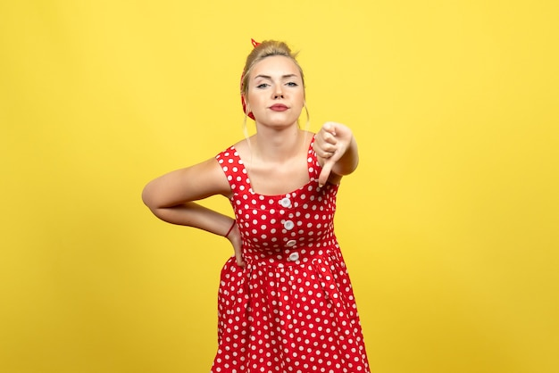 Jovem mulher com vestido de bolinhas vermelhas mostrando sinal diferente em amarelo