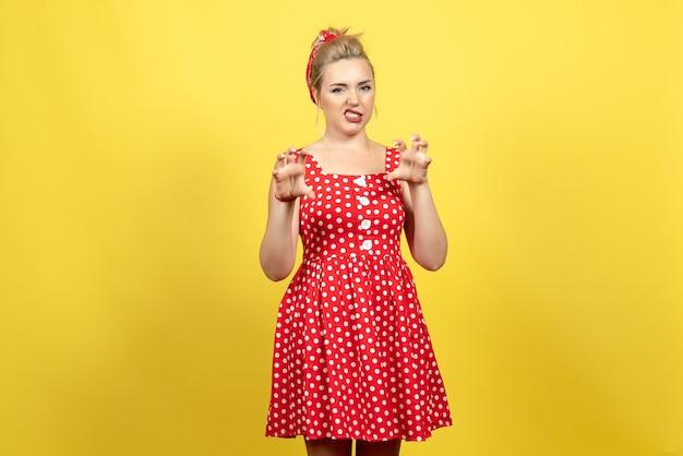 Jovem mulher com vestido de bolinhas vermelhas, posando em amarelo