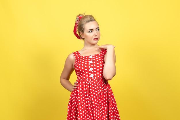 Jovem mulher com vestido de bolinhas vermelhas posando no chão amarelo mulher emoção cor retrô moda fofo