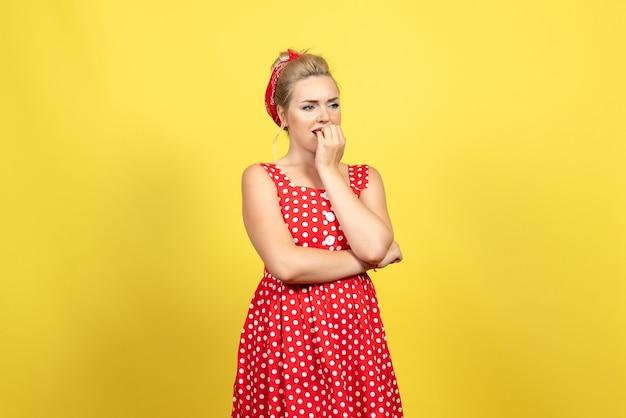 Jovem mulher com vestido de bolinhas vermelhas, sentindo-se nervosa no amarelo