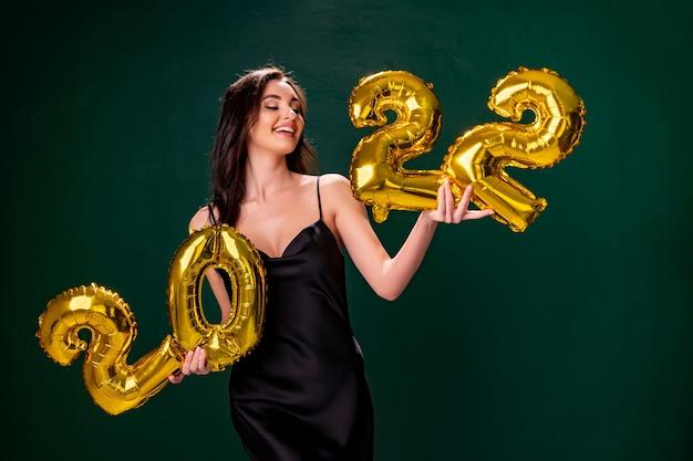 Jovem mulher com vestido de cocktail com maquiagem brilhante, comemorando o ano novo e segurando balões dourados.