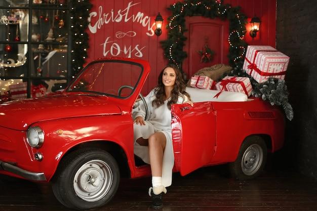 Jovem mulher com vestido de malha, posando em um carro vintage vermelho com decoração de natal e caixas de presente.