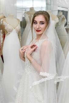 Jovem mulher com vestido de noiva e véu na loja de noivas