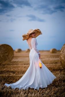 Jovem mulher com vestido de noiva em pé no campo com uma lâmpada nas mãos à noite