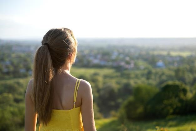Jovem mulher com vestido de verão amarelo em pé num prado verde, apreciando a vista do sol.