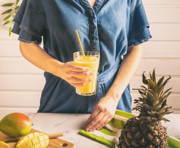 Jovem mulher com vestido jeans, segurando um copo com suco de manga e abacaxi na mão. estilo de vida saudável.