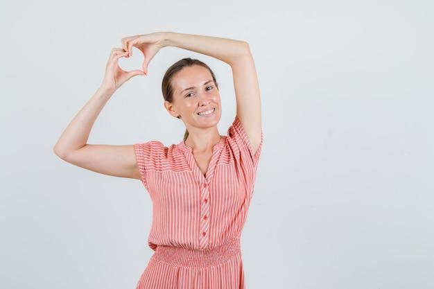 Jovem mulher com vestido listrado, fazendo formato de coração com as mãos e olhando alegre, vista frontal.