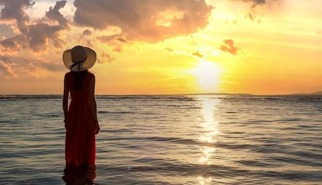 Jovem mulher com vestido longo vermelho e chapéu de palha em pé na água do mar na praia, apreciando a vista do sol nascente no início da manhã de verão.
