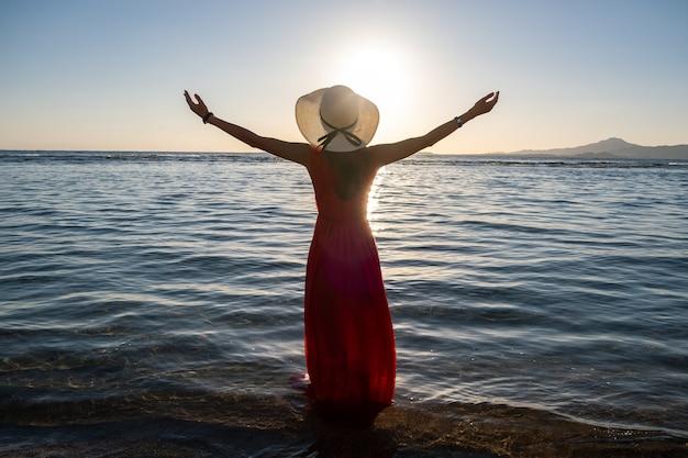 Jovem mulher com vestido longo vermelho e chapéu de palha, levantando as mãos em pé na água do mar na praia, apreciando a vista do sol nascente no início da manhã de verão.