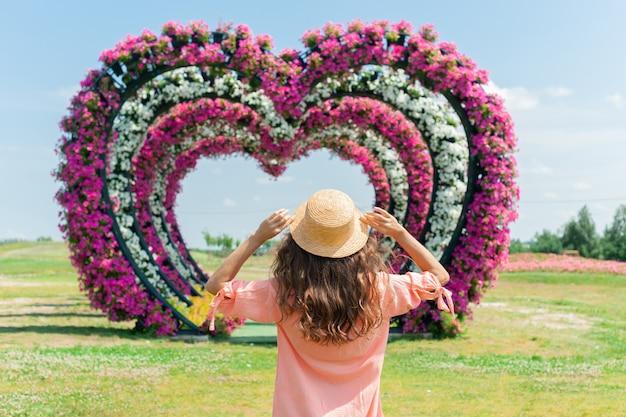 Jovem mulher com vestido rosa e chapéu fica em um fundo de arcos de flores. imagem com foco seletivo no chapéu