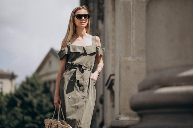 Jovem mulher com vestido verde de pé junto ao edifício antigo