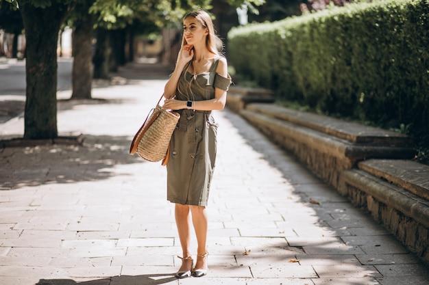 Jovem mulher com vestido verde fora no parque