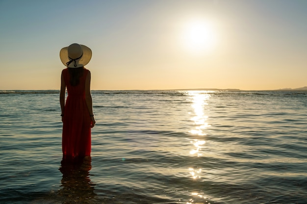 Jovem mulher com vestido vermelho longo e chapéu de palha em pé na água do mar na praia, apreciando a vista do sol nascente na manhã de verão.