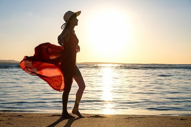 Jovem mulher com vestido vermelho longo e chapéu de palha em pé na praia de areia na costa do mar, apreciando a vista do sol nascente no início da manhã de verão.