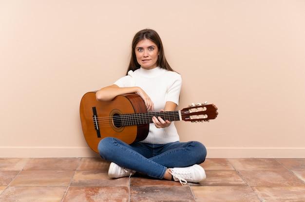 Jovem mulher com violão sentado no chão com dúvidas e com a expressão do rosto confuso