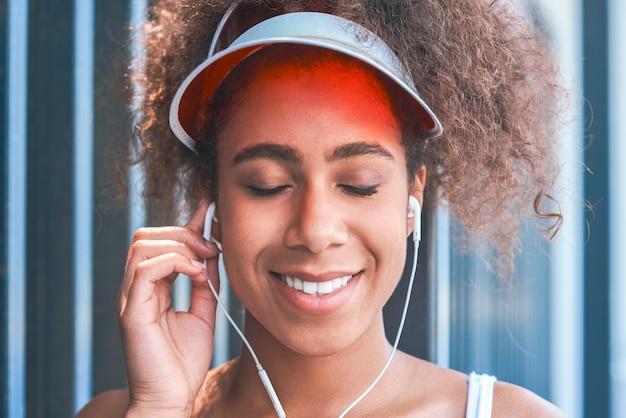 Jovem mulher com viseira de tênis colocando fones de ouvido estilo livre no t