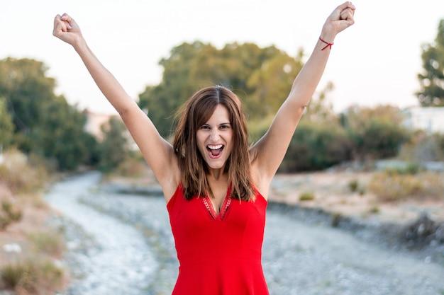 Jovem mulher comemorando a vitória com um vestido vermelho